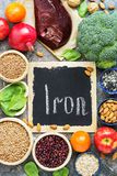 Food with iron, liver, pomegranate, nuts, persimmon, apples, beans, lentils, broccoli, buckwheat, spinach, sesame on a rustic back royalty free stock photography