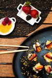 Japanese cuisine served on plates with berries and seeds on wooden table. stock image