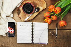 Food Journal and Coffee. Overhead shot of an open food journal book with cell phone, coffee and flowers over a wood table top ready to plan diet. Flat lay top Stock Photography