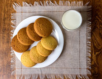 Food, junk-food, culinary, baking and eating concept - close up oatmeal cookies and milk glass royalty free stock photography