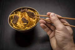 Food knitted from woolen thread lies on a plate, as a Chinese dish of noodles and meat, the human hand holding a wooden spokes lik Stock Photos