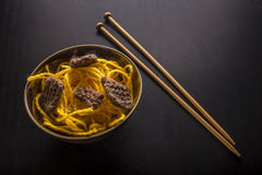 Food knitted from woolen thread lies on a plate, as a Japanese dish of meat and noodles, lie next to the wooden spokes, like stick Royalty Free Stock Photography