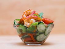 Food. Langoustines salad, beige background. Beautiful appetizer langoustines salad, decorated vegetables cucumber and rukola.  Beige background. Close up. Fried Royalty Free Stock Photography