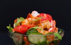 Food. Langoustines salad, black background. Beautiful appetizer langoustines salad, decorated vegetables cucumber and rukola.  Black background. Close up. Fried Royalty Free Stock Images