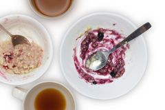 Food leftovers after breakfast for recycling. An overhead photo of dirty spoon and a bowl with porridge and bilberry jam leftovers Royalty Free Stock Photography