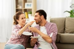 Happy couple eating pizza at home stock images
