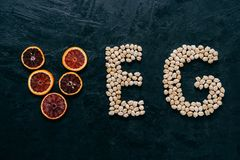Food letters. Garbanzo and slice of citrus fruit in form of veg letters on dark background. Organic ingredients for vegetarians. Healthy products royalty free stock photo