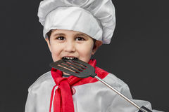 Food, Little boy preparing healthy food on kitchen over grey bac Royalty Free Stock Images