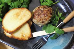 Food, lunch. Meat cutlet with toast, cilantro and parsley on a p stock photo