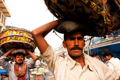 Food market workers suffer huge baskets Stock Photography