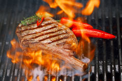 Food meat - beef steak on bbq barbecue grill with flame. Shallow dof Stock Photography
