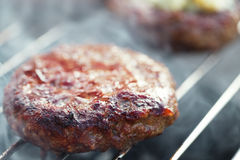 Food meat - burgers on bbq barbecue grill Royalty Free Stock Photos