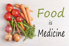Food is Medicine text with assorted vegetables. Assorted vegetables with text `Food is Medicine`on wooden surface. Top view royalty free stock image