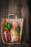 Food mix  inside a paper bag on the wooden background vertical Royalty Free Stock Image