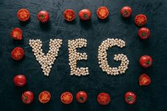 Food and nutrition concept. Horizontal shot of dry garbanzo in form of letter VEG, denoting products for vegans. Tomato frame. Around stock photo