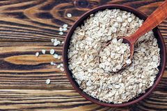 Food. Oatmeal on the table. Dry rolled oat flakes oatmeal in brown bowl on old wooden table. Royalty Free Stock Image