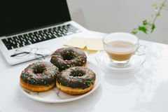 Food in the office. Donuts on working desk. Food in the office. Donuts on working desk Royalty Free Stock Photo