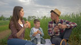 Food outdoors, happy guy with girl and child boy eat bakery while relaxing at family picnic on nature in green field stock video footage