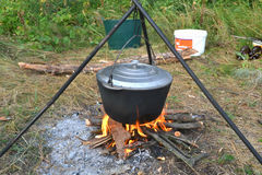 Food over a campfire. Food in a pot on a fire camping in the woods royalty free stock photos