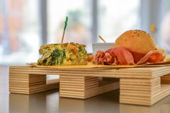 Food party on nice wooden tray. Food party: nice wooden tray with a small sandwich with ham and an omelette with spinach stock images