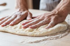 Food pastry prepare baker man hands flatten dough. Food and pastry concept. preparing and cooking skills concept. man hands flattening dough stock photo