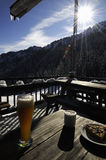 Food on patio at ski resort. A light lunch with beer sitting on a table on an outdoor patio at a ski resort in winter.  High contrast Stock Photography