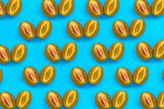 Food pattern of halves of ripe blue plum with bone on bright turquoise paper,. Minimalism style, top view royalty free stock images