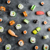Food pattern made of raw sushi rolls on a dark background. Japanese food. Flat lay. Top view. Food pattern made of raw sushi rolls on a dark background. Japanese Royalty Free Stock Photography