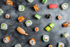 Food pattern made of sushi rolls on dark background. Japanese food. Flat lay. Top view. Food pattern made of sushi rolls on dark background. Japanese food. Flat Stock Photography