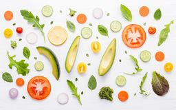Food pattern with raw ingredients of salad, lettuce leaves, cucumbers, tomatoes, carrots, broccoli, basil ,onion and lemon flat l. Ay on white wooden background royalty free stock photography