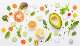 Food pattern with raw ingredients of salad, lettuce leaves, cucu. Mbers, tomatoes, carrots, broccoli, basil ,onion and lemon flat lay on white wooden background royalty free stock image