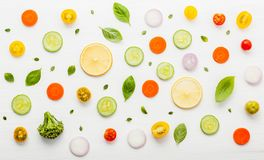 Food pattern with raw ingredients of salad, lettuce leaves, cucumbers, tomatoes, carrots, broccoli, basil ,onion and lemon flat l. Ay on white wooden background stock photo
