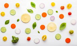 Food pattern with raw ingredients of salad, lettuce leaves, cucumbers, tomatoes, carrots, broccoli, basil ,onion and lemon flat l. Ay on white wooden background royalty free stock images