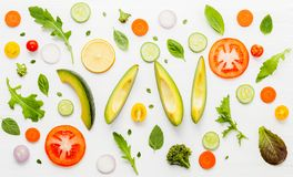 Food pattern with raw ingredients of salad, lettuce leaves, cucumbers, tomatoes, carrots, broccoli, basil ,onion and lemon flat l. Ay on white wooden background royalty free stock photo