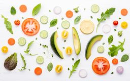 Food pattern with raw ingredients of salad, lettuce leaves, cucu. Mbers, tomatoes, carrots, broccoli, basil ,onion and lemon flat lay on white wooden background royalty free stock photography