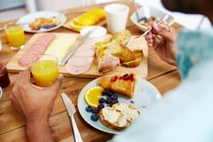 Close up of man eating croissant with orange juice Royalty Free Stock Images