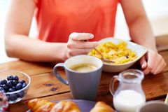 Close up of woman eating cereals with coffee Stock Photo