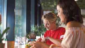 Female friends eating at restaurant. Food and people concept - female friends eating at restaurant or cafe