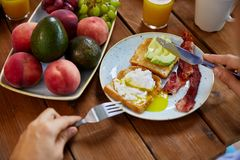 Man eating toast with pouched egg and bacon. Food and people concept - hands of man eating toast with pouched egg, avocado and bacon with fork and knife Stock Photography