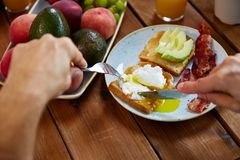 Man eating toast with pouched egg and bacon. Food and people concept - hands of man eating toast with pouched egg, avocado and bacon with fork and knife Royalty Free Stock Photography