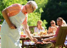 Senior man cooking meat on barbecue grill outdoors. Food, people and family time concept - senior men cooking meat on barbecue grill at summer garden bbq party Royalty Free Stock Photography