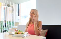 Woman with coffee calling smartphone at restaurant Stock Image