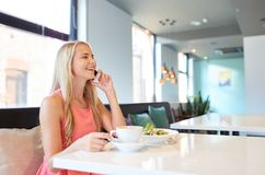 Woman with coffee calling smartphone at restaurant Royalty Free Stock Images