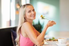 Happy young woman eating lunch at restaurant Royalty Free Stock Photos