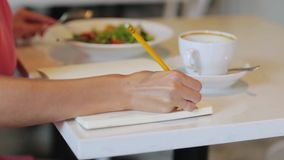 Woman or reviewer rating dish at restaurant. Food, people and leisure concept - woman or reviewer eating lunch at restaurant, rating dish and writing to notebook stock footage