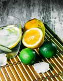 Lime and lemon splash with ice and some detox water. Food photo of fresh lime and lemons. This is perfect for background or magazines related to food and kitchen Stock Photography