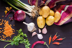 Food photo with fresh organic vegetables on dark wooden rustic background, top view. Green onions, scallions, red onion, spring garlic, new potatoes, parsley royalty free stock image