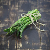 Food Photo green asparagus. Tied with string with a bow on dark wooden board, healthy food, vegetables, delicious healthy food stock photos