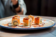 Food photographer takes picure of sushi rolls. Close up delicious sushi rolls on plate with blurred photographer in background Stock Images