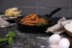 Food photography. Cooking pasta in a frying pan, basil greens, eggs and flour on the table royalty free stock images